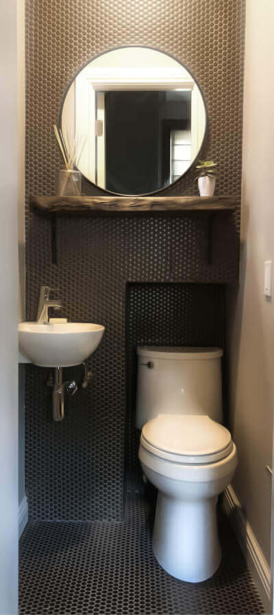 This tiny powder room uses an open shelf, large mirror and simplification of color and restricted materials.