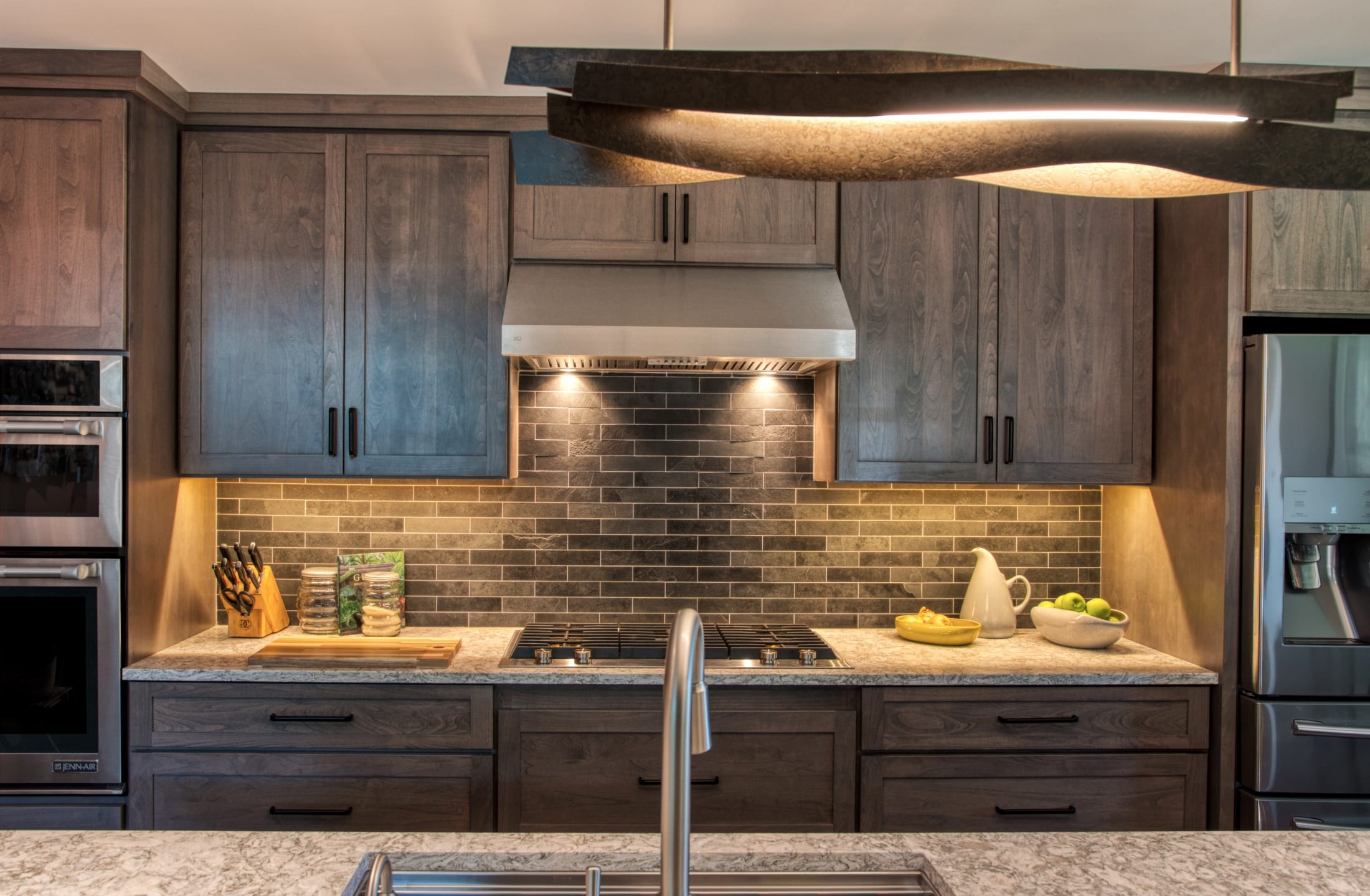 Sculptural Island lighting complements other earthy tones in this kitchen
