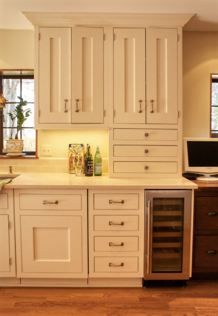 Creme shaker kitchen cabinets and wine service area in Tudor home